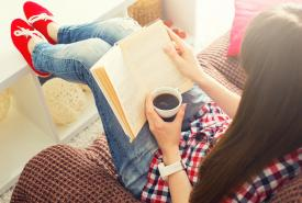 Woman on sofa, reading and enjoying a cup of coffee